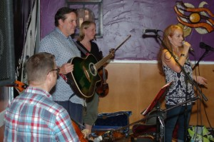LaRaine from BC Songwriters, introducing Dan Beer, Jon Goheen and Kat Goheen, performing at the Songwriter Showcase
